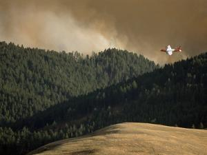 Firefighting Plane Prepares to Drop Retardant on a Forest Fire by Gordon Wiltsie
