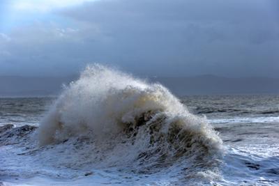 Huge Waves Crash Against a Stone Jetty at Criccieth, Gwynedd, Wales, United Kingdom, Europe by Graham Lawrence