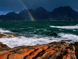 Rainbow Dipping into Coles Bay During Stormy Weather, Freycinet National Park, Tasmania, Australia by Grant Dixon
