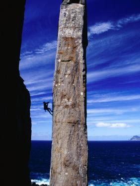 Rock-Climber Ascending the Totem Pole Rock Stack on the Tasman Peninsula, Australia by Grant Dixon