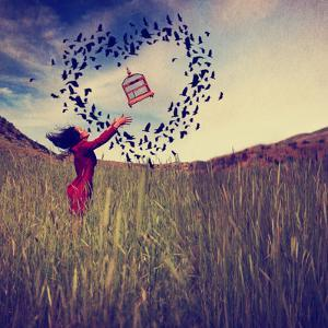A Girl in a Field Tossing a Birdcage in the Air with Birds Flying in the Shape of a Heart Toned Wit by graphicphoto