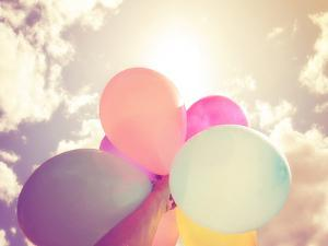 A Person Holding Multi Colored Balloons Done with a Retro Vintage Instagram Filter Effect by graphicphoto