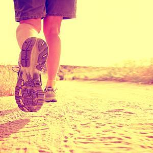 An Athletic Pair of Legs on a Dirt Path during Sunrise or Sunset - Healthy Lifestyle Concept Toned by graphicphoto