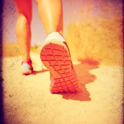An Athletic Pair of Legs Running or Jogging on a Path during Summer Toned with a Soft Vintage Insta by graphicphoto
