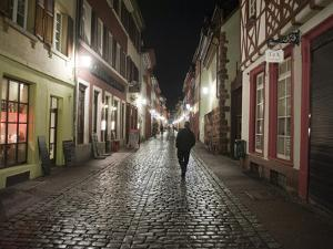 A Man Walks Down a Cobbled Street at Night by Greg Dale