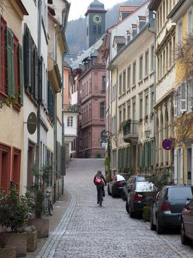 A Woman Rides a Bike Up a Cobbled Street in the Morning by Greg Dale