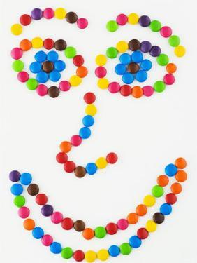Coloured Chocolate Beans Forming a Smiling Face by Greg Elms
