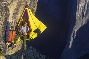 Climber in His Hanging Camp Sleeps on the Side of a Mountain. by Greg Epperson