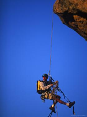 Rock Climber Hanging off Cliff by Greg Epperson