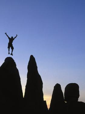 Silhouette of Man Jumping on Top of Rock by Greg Epperson