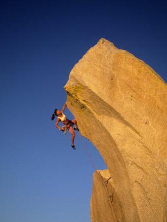 Woman Climbing Cliff Wall