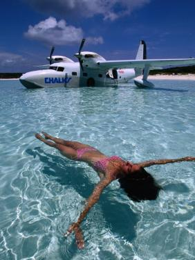 Female Floating in Crystal Waters in Front of Seaplane, Bahamas by Greg Johnston