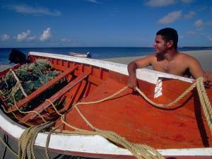 Fisherman Tends His Boat on the Beach, Isla Margarita, Venezuela by Greg Johnston