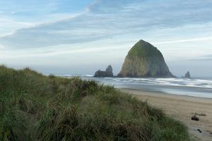 Hay Stack Rock on the sandy beach at Cannon Beach, Oregon by Greg Probst