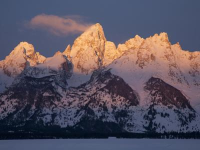 A Cloud Trails Off the Summit of the Grand Teton at Sunrise by Greg Winston