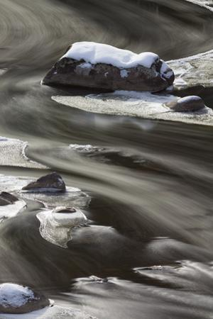 A long exposure creates blurred lines of water around rock and ice by Greg Winston