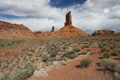 Castle Butte, a Sandstone tower, under partly cloudy skies. by Greg Winston