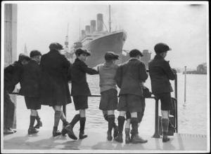Group of Boys Lean Against the Dock Railings and Watch a Steamship Being Built