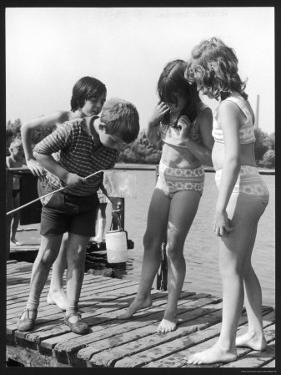 Group of Children Including Girls in Bikinis Inspect Their Net for Fish