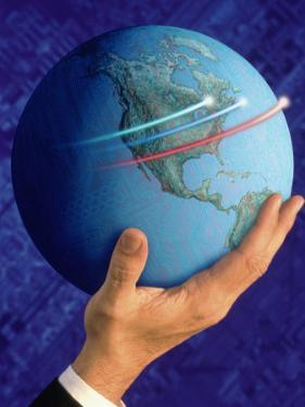 Businessman's Hand Holding Globe by Guy Crittenden
