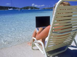 Woman on Beach with Laptop by Guy Crittenden