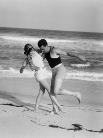 A Couple in 1920's Bathing Costumes Frolic on a Beach, Circa 1965 by H. Armstrong Roberts