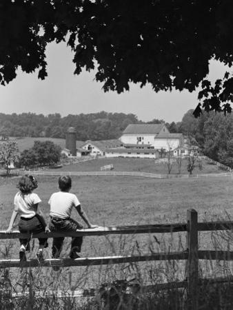 Boy and Girl Sitting on Fence, Overlooking Farm Fields by H. Armstrong Roberts