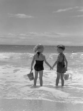 Boy and Girl Standing on Beach, Holding Hands, Rear View by H. Armstrong Roberts