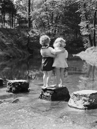 Boy and Girl Standing on Rock Path in Stream, With Arms Around Each Other by H. Armstrong Roberts