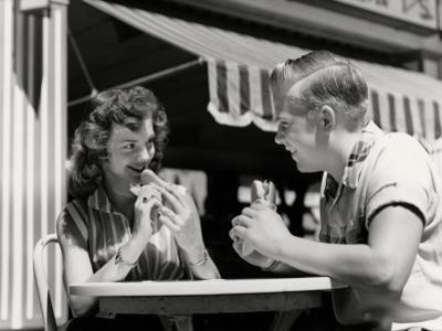 Couple Eating Hot Dogs by H. Armstrong Roberts
