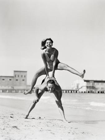 Couple Playing Leapfrog on Beach, Woman Jumping Over Man by H. Armstrong Roberts