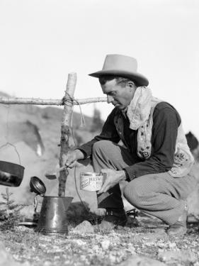 Cowboy Kneeling By Campfire Pouring Coffee by H. Armstrong Roberts