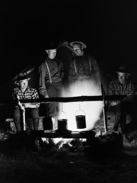 Four Men Wearing Plaid Shirts, Suspenders and Hats, Cooking Over Campfire by H. Armstrong Roberts