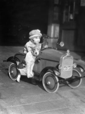 Girl in Toy Pedal Car With Dog Sitting on Running Board by H. Armstrong Roberts