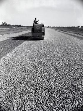 Highway Construction Worker Operating Heavy Machinery on Loose Gravel Road by H. Armstrong Roberts
