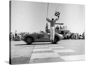 Man jumping waving checkered flag by H^ Armstrong Roberts
