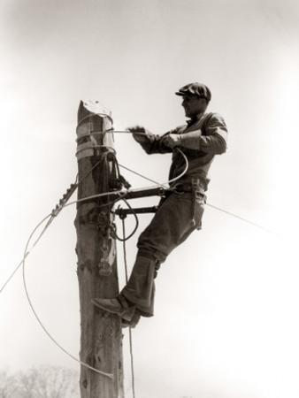 Man Worker, Working Atop Utility Pole, Installing Electric Wires For Power Utilities by H. Armstrong Roberts