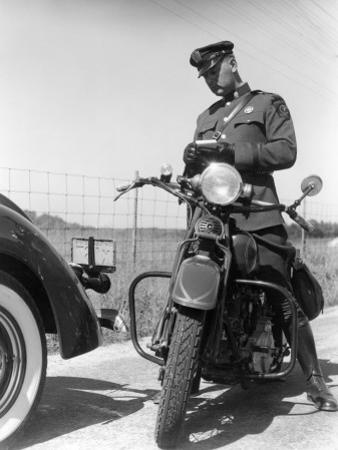 Policeman on a Motorcycle Writing a Ticket by H. Armstrong Roberts