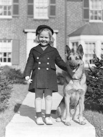 Smiling Girl With a German Shepherd Wearing a Six Button Navy Overcoat by H. Armstrong Roberts