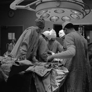 Surgical Team of Five Huddled Together, Operating on Patient by H. Armstrong Roberts
