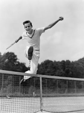 Teen in Tennis Whites Hurdleing the Net With Arms by H. Armstrong Roberts