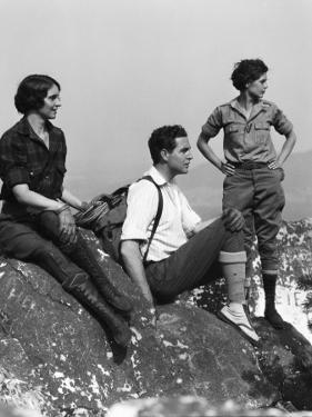 Three People in Hiking Clothes, Atop Mountain on Rock Outcrop, Looking Off Into Distance by H. Armstrong Roberts