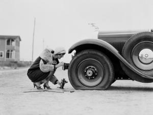 Woman Changing Flat Tire on Car by H. Armstrong Roberts
