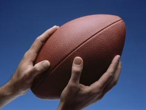 Hands Holding Football with Blue Background