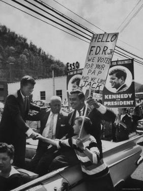 John F. Kennedy and Franklin D. Roosevelt Jr. Shaking Hands with Boy During Parade by Hank Walker