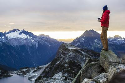 Woman Drinks Her Coffee On Top Of A Mountain In The Morning Looking Out Into The Cascade Mts In WA