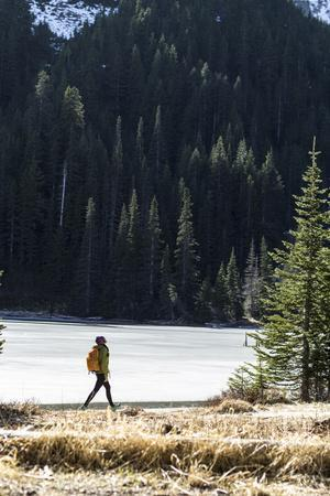 Woman Hiker Walks Alongside A Frozen Lake In The Olympic Mountain High Country During Winter In WA