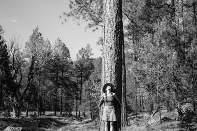 Woman Stands With Her Arms Wrapped Around A Ponderosa Pine Tree Looking Up And Smiling