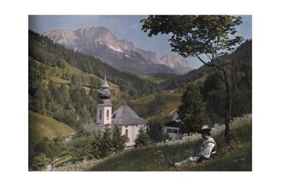 A Scenic View of a Ramsau Church in Front of Untersberg Mountain by Hans Hildenbrand