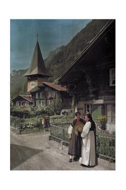 Locals Stand Outside of a Cottage on the Streets of Meiringen by Hans Hildenbrand